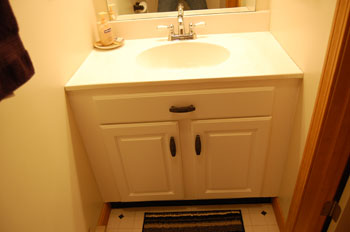 classic kitchen photo of a refaced bathroom vanity in white rigid thermal foil, with square raised panels.