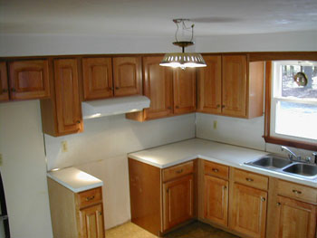 After picture of a refaced classic kitchen with an arch raised panel top and square raised panel base doors, in natural cherry